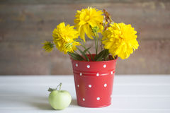 Yellow flowers and apple. On a wooden background royalty free stock photography