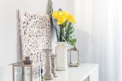 Yellow flowers in ceramic vase with wooden candlesticks and lantern decorating a shelf. In a living room royalty free stock photo