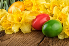 Yellow flowers with Easter eggs on old wood Stock Photography