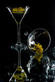 Yellow Flowers and Glasses. Martini glasses containing water with yellow flowers in them. One glass is standing and the other one is fallen, on a black Royalty Free Stock Photo