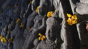 Yellow flowers kon Apsara angle sculpture Royalty Free Stock Photography