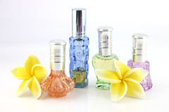 The yellow flowers and Orange,Blue,Green,Violet Perfume bottles. Royalty Free Stock Photos