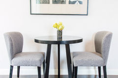 Yellow flowers in the vases on the table and chairs by the wall. Royalty Free Stock Image