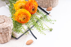 Yellow flowers, wicker baskets and a notebook Stock Images