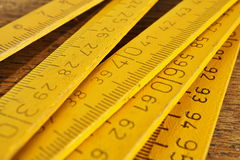 Yellow folding meter on the wooden background as a symbol of precision Royalty Free Stock Photography
