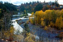 Yellow foliage trees in Hood River, Oregon. View from above on Hood River in fall twilight. City bridge over river and yellow trees stock photo