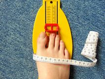 Yellow foot measurement device with naked foot upon with measuring tape Royalty Free Stock Images