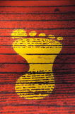 Yellow Footprint Against Red Background. Bright yellow footprint against red stripe background royalty free stock photography