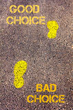 Yellow footsteps on sidewalk from Bad Choice to Good Choice message. Concept image Royalty Free Stock Photo
