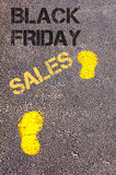 Yellow footsteps on sidewalk towards Black Friday Sales message. Retail sales Conceptual image Stock Image