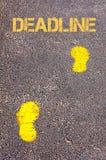 Yellow footsteps on sidewalk towards Deadline message Royalty Free Stock Photo
