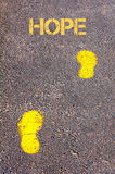 Yellow footsteps on sidewalk towards Hope message Stock Photos