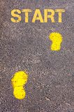 Yellow footsteps on sidewalk towards Start message Stock Image