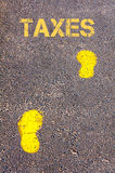 Yellow footsteps on sidewalk towards Taxes message Stock Photo