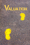 Yellow footsteps on sidewalk towards Valuation message Stock Photo