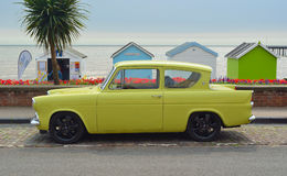 Yellow Ford Anglia motor car on seafront road in front of beach huts. Royalty Free Stock Images
