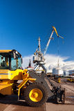 Yellow forklift and crane at loading and unloading of cargo in t. Yellow forklift and crane at unloading and loading cargo at the port on a background of blue Royalty Free Stock Image