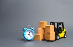 Yellow Forklift truck with cardboard boxes and a blue alarm clock. Express delivery concept. Temporary storage, limited offer royalty free stock image