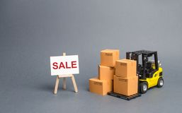 Yellow Forklift truck with cardboard boxes and stand with the word sale. sale of goods, big discounts on goods of the outgoing. Season. commodity exchange with royalty free stock images