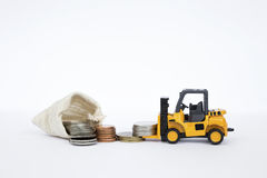 Yellow forklift truck lifting coins with pile of coins in canvas bag Stock Images