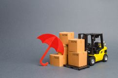 Yellow Forklift truck near carton boxes with a pattern of shopping carts and umbrella. insurance, providing warranty on purchased royalty free stock images