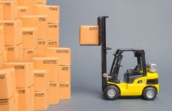Yellow Forklift Truck Picks Up A Box On A Pile Of Boxes. Service Storage Of Goods In A Warehouse, Delivery And Transportation Stock Photography