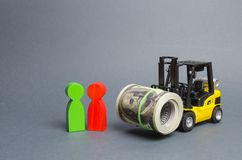 Yellow Forklift truckcarries a large bundle of dollars, a customer and seller. Investments, Preferential cheap loans for business. Development. Upgrading royalty free stock images