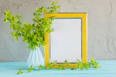 Yellow frame mockup and vase with fresh green branches. Stock Photos