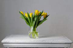 Yellow, fresh tulips in a vase on a wooden table. Royalty Free Stock Photos