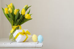 Yellow, fresh tulips in a vase on a wooden table. Gift and Easte Royalty Free Stock Image