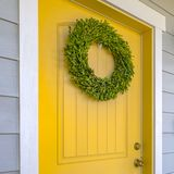 Yellow front door with ornamental green wreath. Simple wreath made from bright green leaves on the front door of a house. The simple wreath hangs on a white stock images