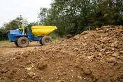 Yellow front tipper dumper working in construction site. stock image