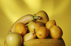 Yellow Fruit. A heap of yellow fruits against a yellow background Stock Photos