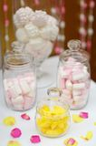 Yellow fruit candy and marshmallow in glass jars Stock Photos