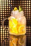 Yellow fruit cocktail lemonade with fresh lemon in vintage jar stock images