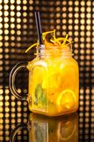 Yellow fruit cocktail lemonade with fresh lemon in vintage jar royalty free stock photography