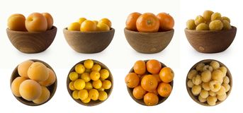 Yellow fruits and berries isolated on white background. Fruits in a wooden bowl with copy space for text. Apricots, yellow plums,. Tangerines and raspberries Stock Photo