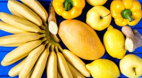 Yellow fruits and vegetables isolated on a blue background Stock Photos