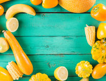 Yellow fruits and vegetables on a turquoise wooden background Stock Images