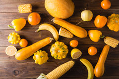 Yellow fruits and vegetables on a wooden background. Colorful festive still life. Stock Photos