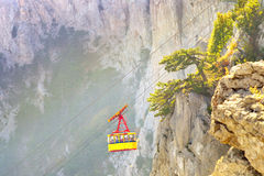 Yellow Funicular Cable with cabin high with Rocky Mountains on background Stock Images