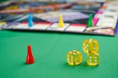 Yellow game dice for board game on a green background royalty free stock image