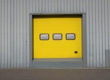 Yellow garage door with three windows in a grey metal wall stock photos