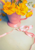 Yellow garden flowers in pink cup and ribbon royalty free stock photos