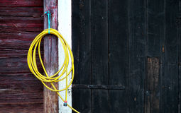 Yellow garden hose. Hanging on wodden wall stock image
