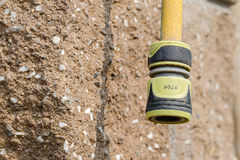 Yellow garden hose with the fixing coupling with the inscription Royalty Free Stock Photo