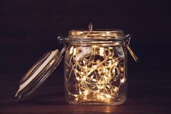 Yellow garland in jar. On wooden background in dark. Concept New year royalty free stock images