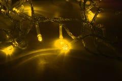Yellow garland lights on black background. Macro royalty free stock photos