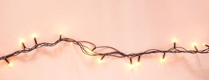Yellow garland on a pink background. Holiday Christmas concept. Banner format stock image