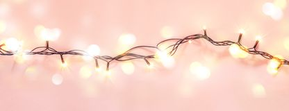 Yellow garland on a pink background. Holiday Christmas concept.  stock image